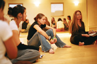 Teen girls and an adult woman sit in a circle.